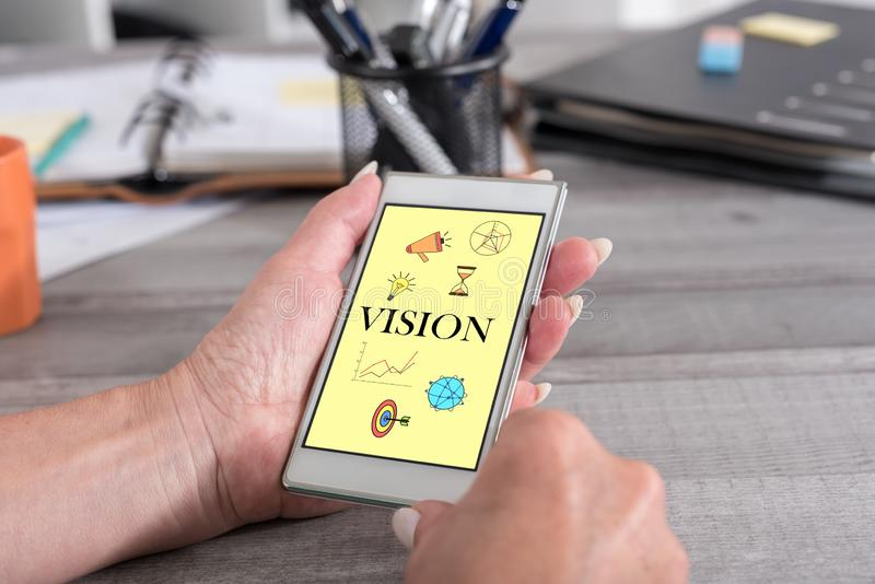 Vision concept on a smartphone. Female hand holding a smartphone with vision concept royalty free stock photography