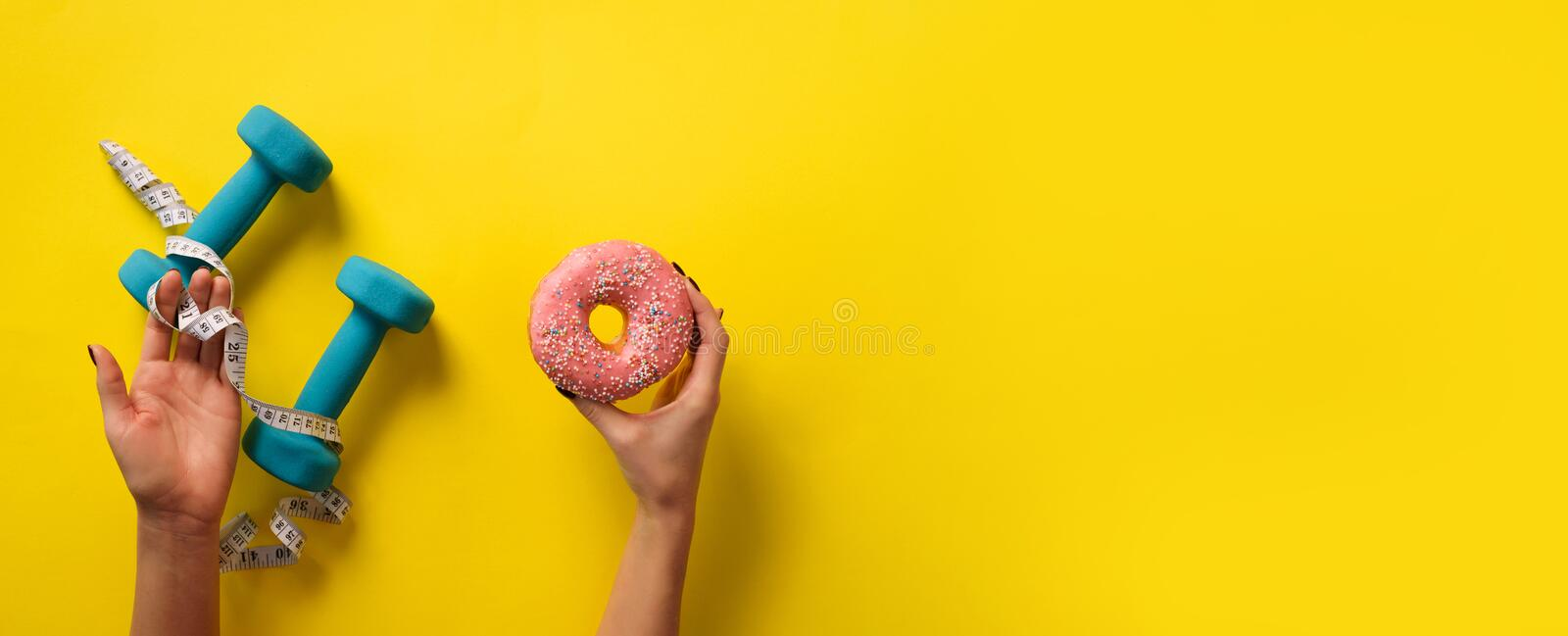 Female hand holding sweet donut, measuring tape, dumbbells over yellow background. Top view, flat lay. Weight lost, sport, fitness royalty free stock images