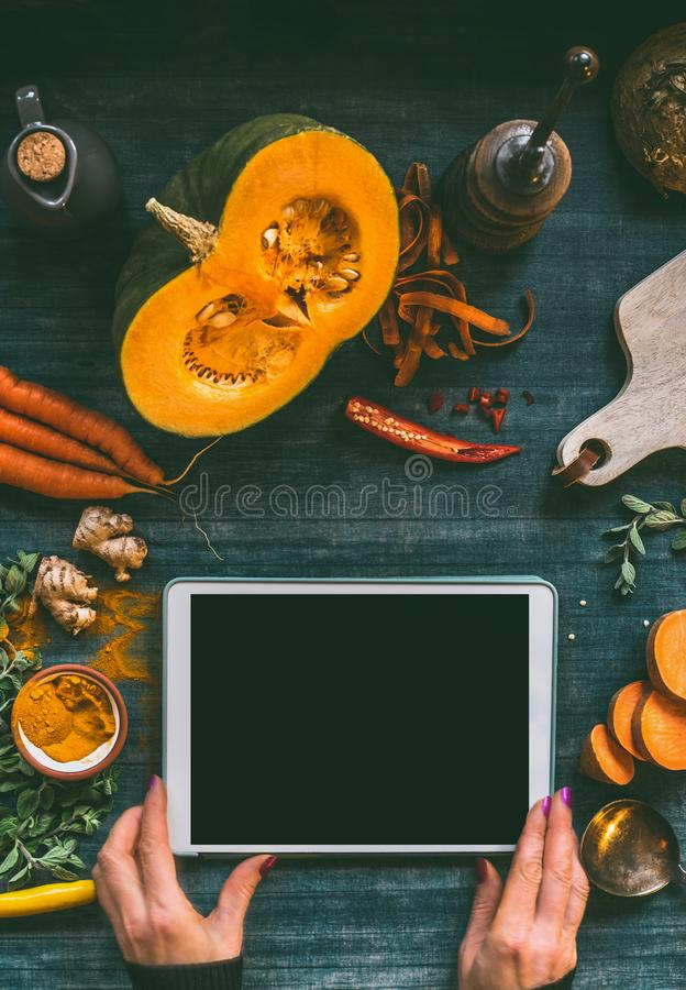 Female hand holding tablet pc with blank black screen mock up on kitchen table background with pumpkin and vegetables ingredients stock photo