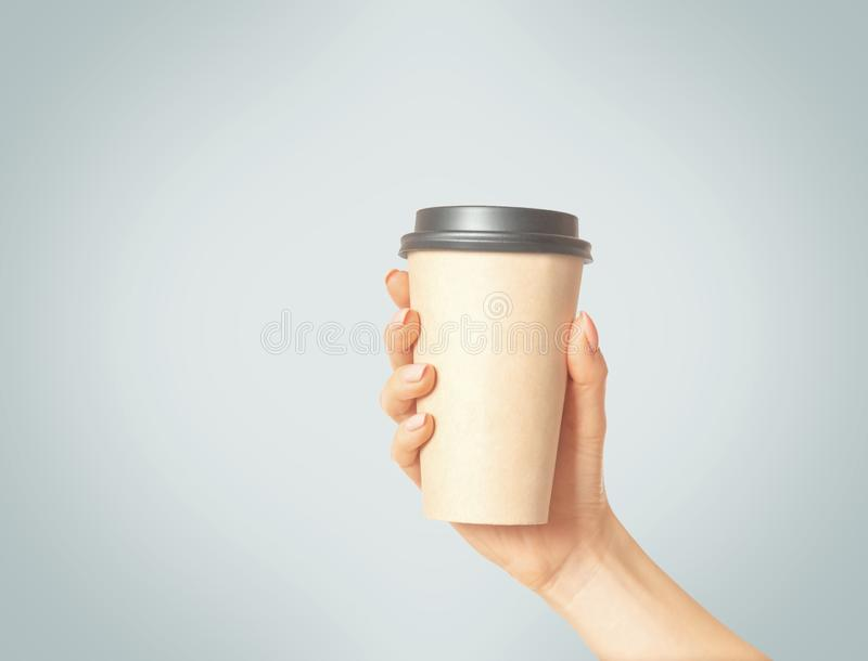 Female hand holding take away paper cup of coffee. royalty free stock image