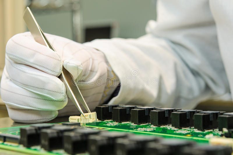 Female hand holding tweezers and installing connector on PCB. In turnkey solutions high-tech manufacturing royalty free stock image