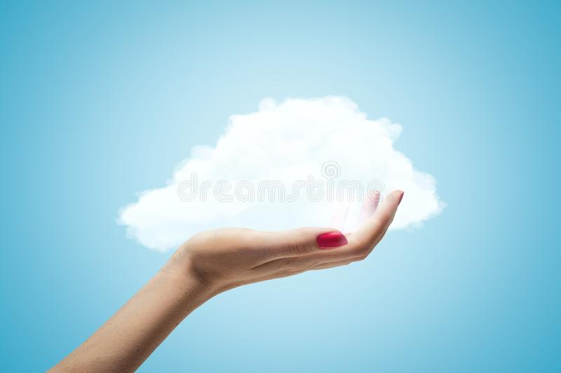 Female hand holding white cloud on blue background stock photos