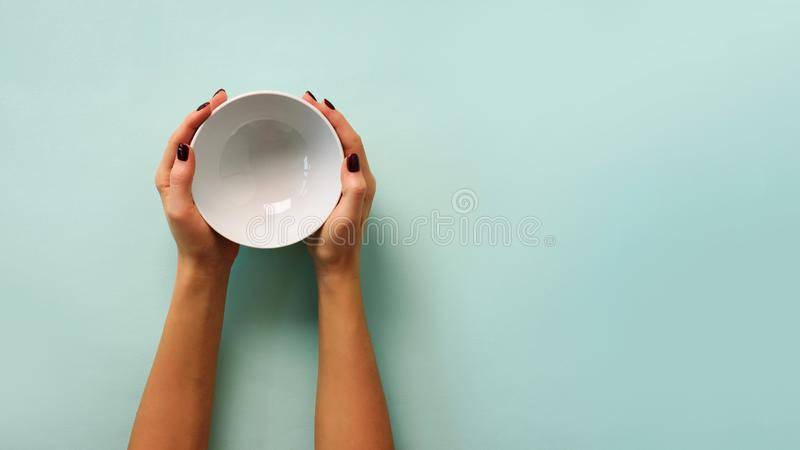 Female hand holding white empty bowl on blue background with copy space. Healthy eating, dieting concept. Banner royalty free stock photo