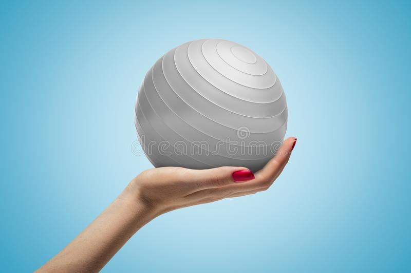 Female hand holding white fitball on blue background stock photos