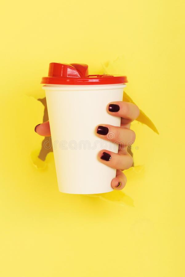 Female hand holding white paper mug on yellow background. Take away coffee cup concept. Mock up with copy space stock image