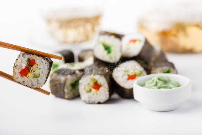 Female hand holding wooden sticks Philadelphia roll with salmon royalty free stock photography
