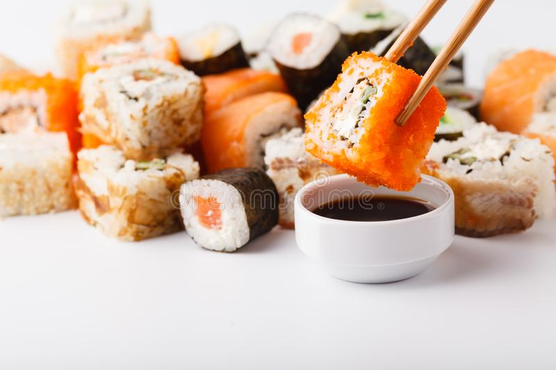 Female hand holding wooden sticks Philadelphia roll with salmon royalty free stock images