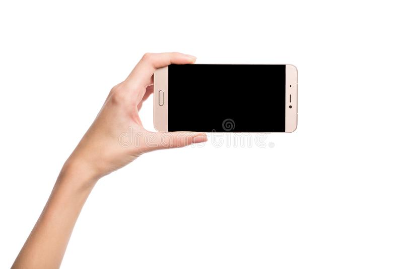 The hand holds the smartphone. Blank screen. Isolated on white. Female hand holds a black smartphone. Empty screen. Isolated on white stock image