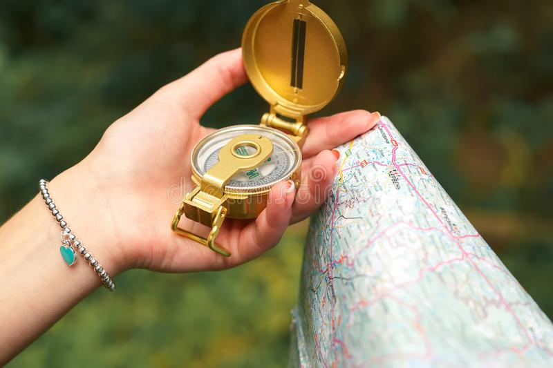 Female hand holds compass and map royalty free stock photography