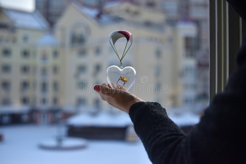 A female hand holds a glass transparent heart with a big ring inside stock photography