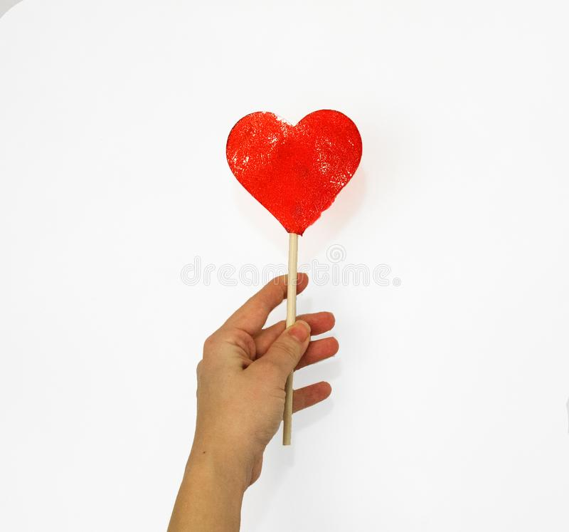 A female hand holds a lollipop on a heart shaped stick. stock photography