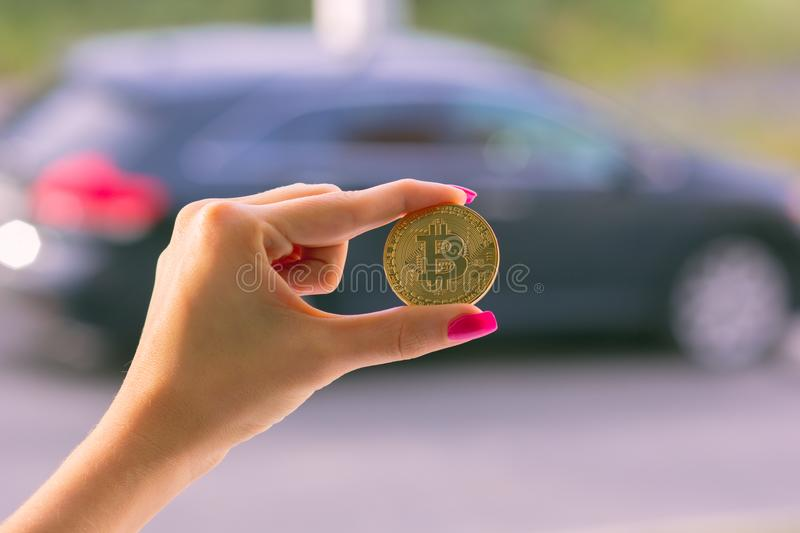 A female hand holds one bitcoin, in a blurry background a car stock photo