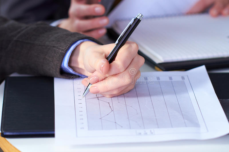 Female hand holds pen over graph stock photography