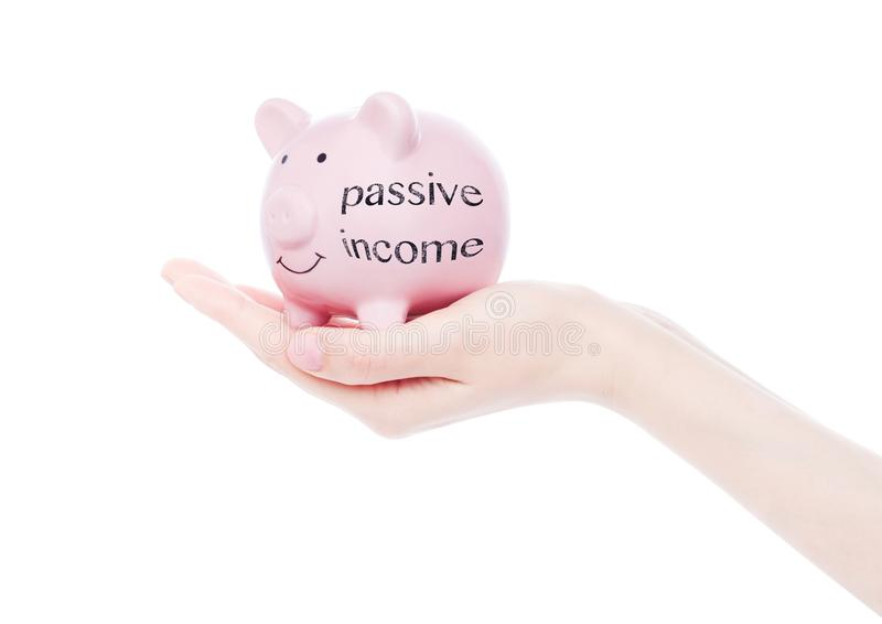 Female hand holds piggy bank passive income text. Female hand holds piggy bank with passive income concept text royalty free stock images