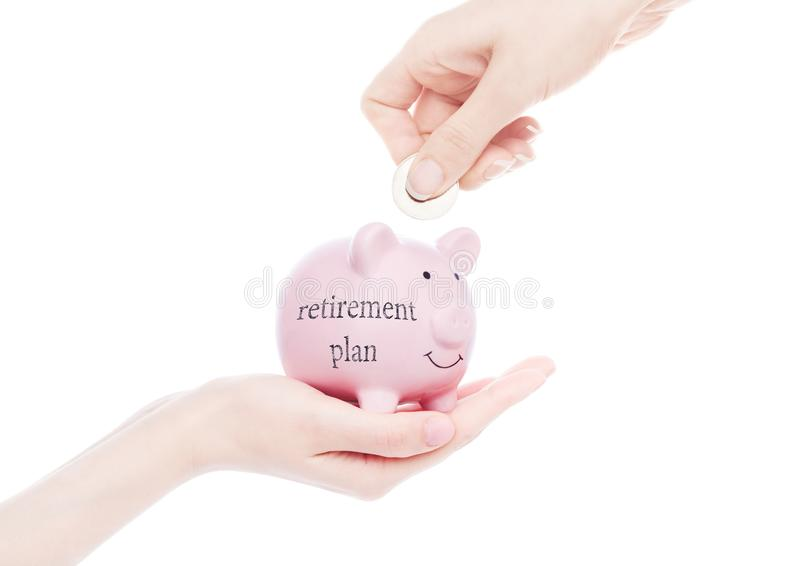 Female hand holds piggy bank retirement plan. Female hand holds piggy bank with retirement plan concept text hand putting coin inside on white background stock photos