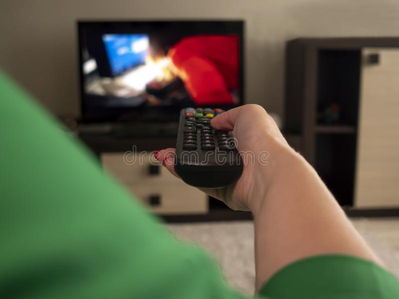 Female hand holds TV remote, rear view royalty free stock photo