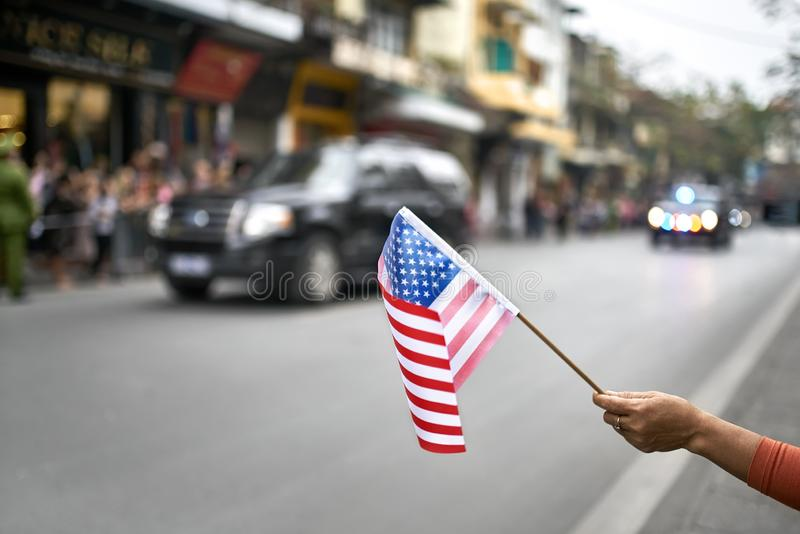 Citizen with flag welcomes diplomatic escort car passage. Female hand holds the USA flag on the blurred background of the moving cars of the american diplomatic stock photo