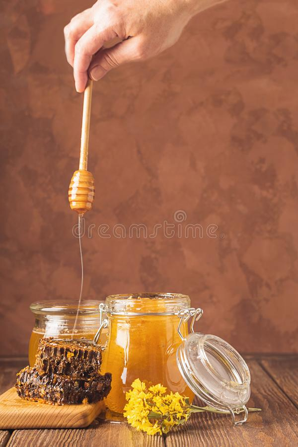 The female hand holds a wooden spoon from which golden honey flows down. Bee aromatic honey on a wooden background . The female hand holds a wooden spoon from stock images