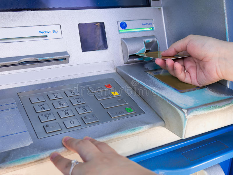 Female hand inserting ATM card into ATM bank machine. To withdraw money royalty free stock photo