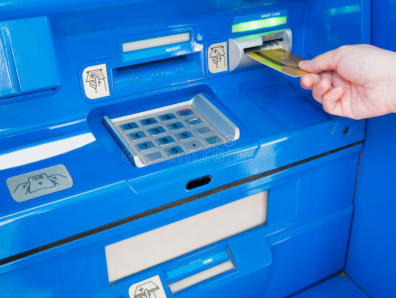Female hand inserting ATM card into ATM bank machine. To withdraw money stock images