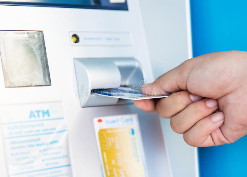female hand inserting ATM card into bank machine to withdraw mon royalty free stock photography