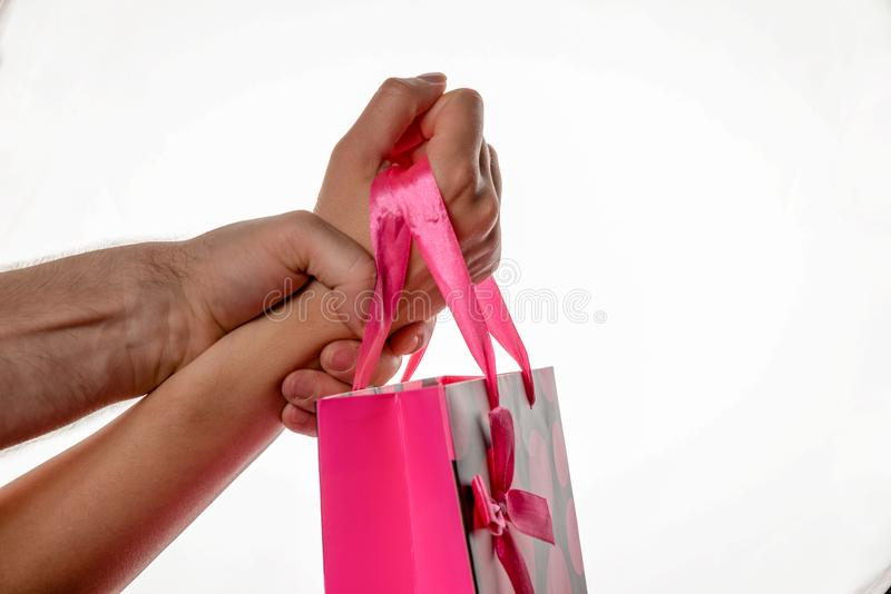 Female hand is keeping pink package with blow. Male hand is keeping female hand strongly. Buy Nothing Day. stock photography