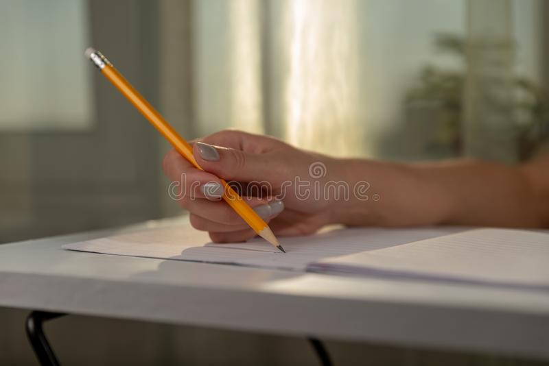 Female hand is keeping yellow pencil and is writing/painting in the notebook in a ruler at the white table. There are window, curt stock photography