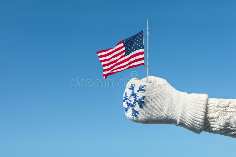 Female hand in a knitted mitten with a snowflake with an American flag on the blue sky background. Hand Thumb Up and good symbol. USA victory and freedom royalty free stock photography
