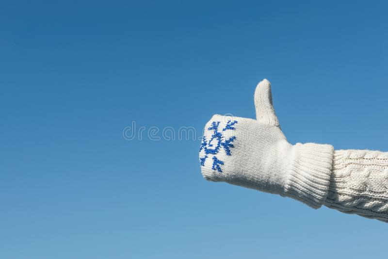 Female hand in a knitted mitten with a snowflake on the blue sky background. Hand Thumb Up gesture and good symbol. stock image