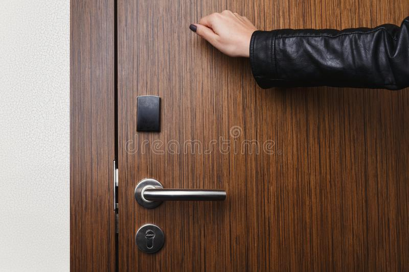 Hand knocking on hotel door with electronic lock. Female hand knocking on wooden hotel door with electronic lock. Security, room service concept, copy space stock photo