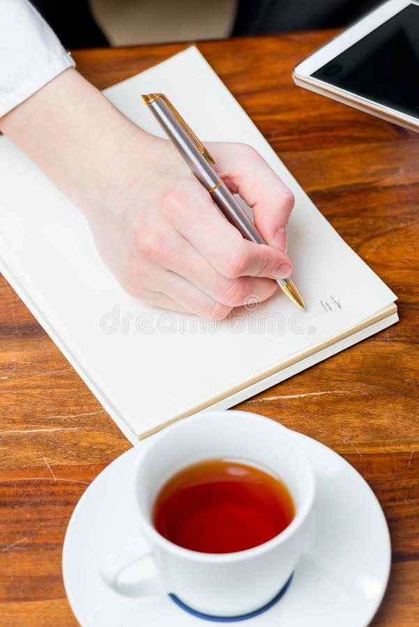 Female hand makes a note in a notebook with a pen, top view of a. Close-up royalty free stock photography