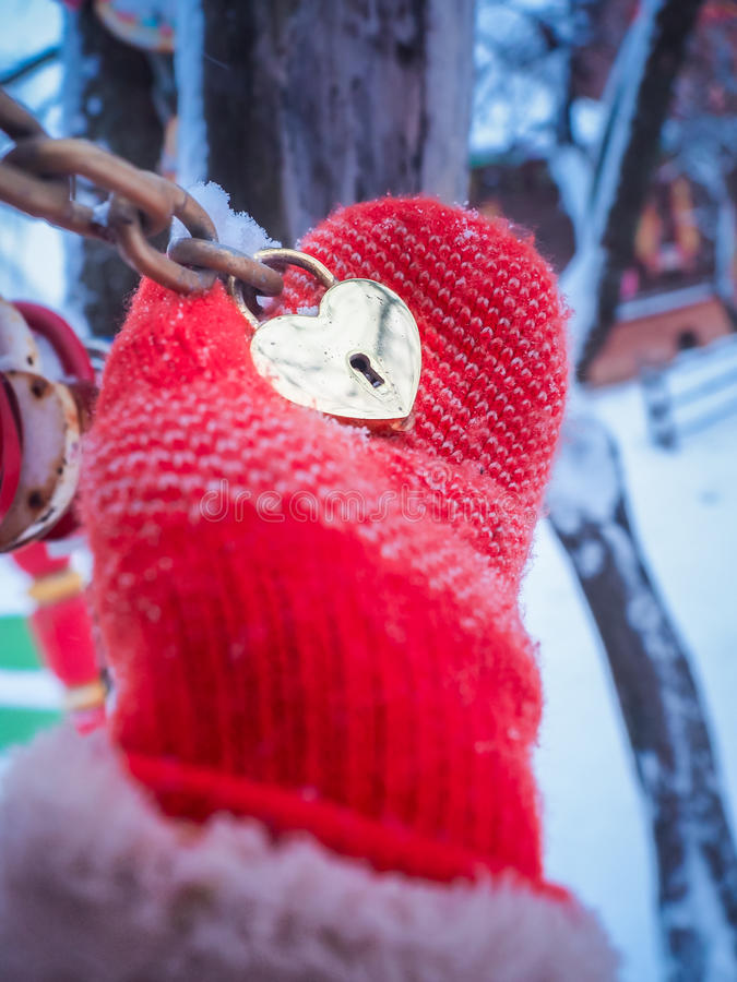 Female hand mitten holding golden padlock in form of heart outdoor in winter time. Valentine Holiday Concept stock images