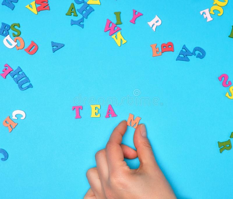 Female hand and multicolored wooden letters of the English alphabet. On a blue background, inscription team stock photography