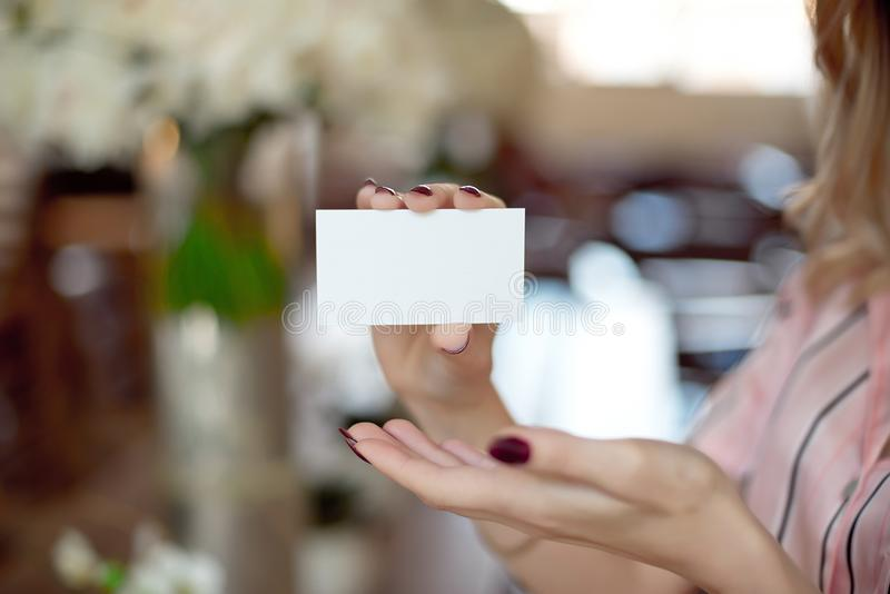 Female hand with neat manicure holding white empty blank business card. stock photos