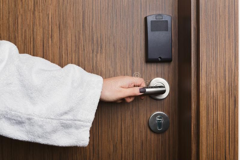 Female hand opening hotel room door knob. Woman in white bathrobe enter room after spa procedure or swimming pool, copy space stock photo