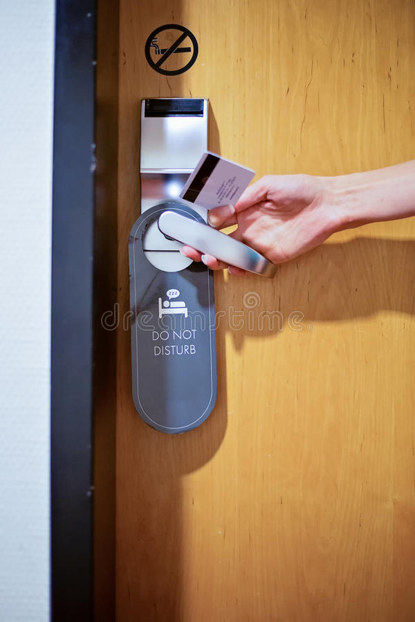 Female hand opening a hotel room door with a sign do not disturb. And no smoking royalty free stock photography