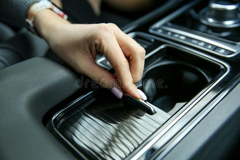 Female hand opens the Cup holder in the car royalty free stock image