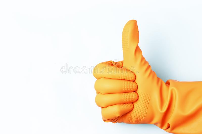 Female hand in orange rubber gloves with raised up his thumb on a white background stock photography