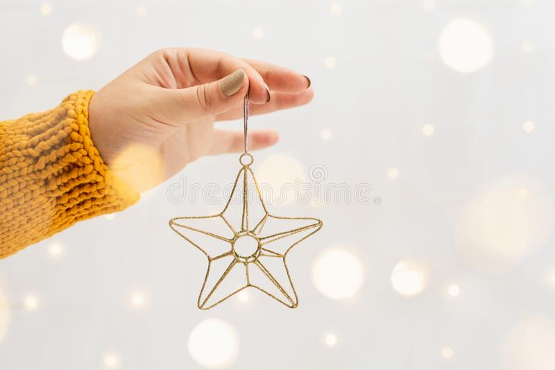 Female hand in orange sweater holding golden Christmas star with garland bokeh on background. Woman hand in orange sweater holding golden Christmas star with stock images