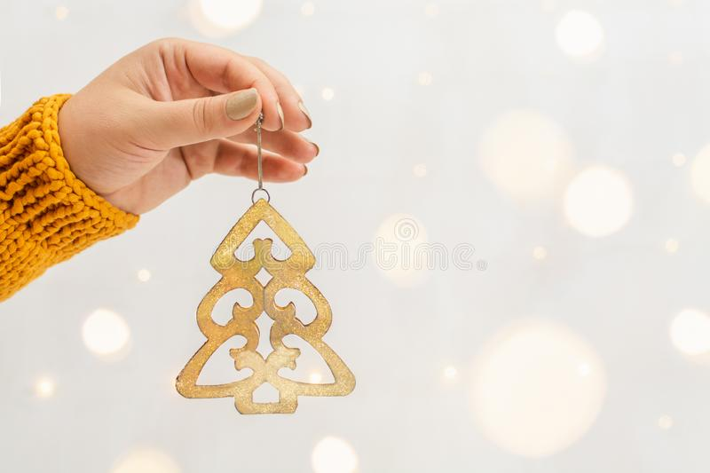 Female hand in orange sweater holding golden Christmas tree with garland bokeh on background. Woman hand in orange sweater holding golden Christmas tree with royalty free stock photos