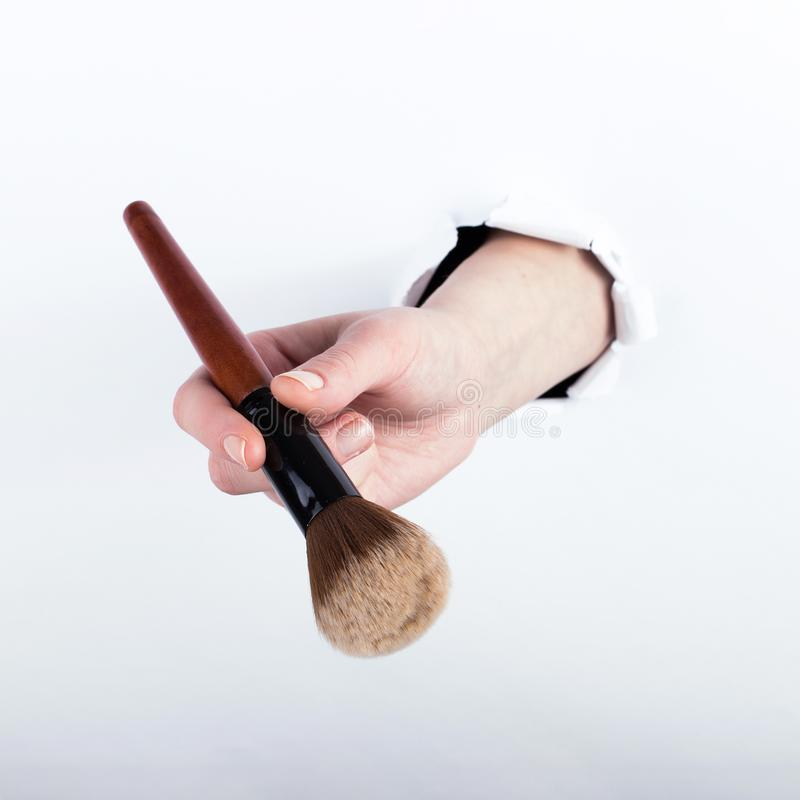Female hand out of a hole in paper, holding a large powder brush. Isolate on white background stock photos