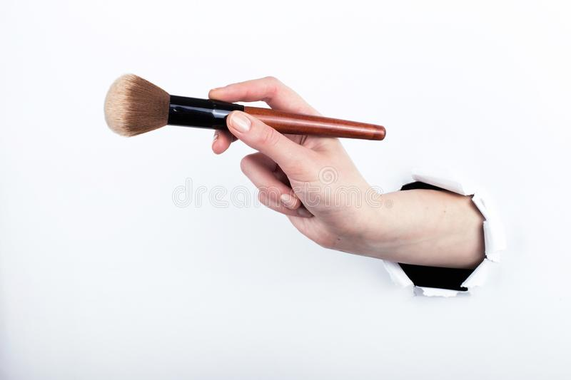 Female hand out of a hole in paper, holding a large powder brush. Isolate on white background stock photo
