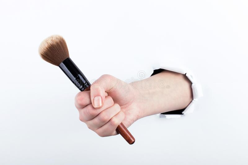 Female hand out of a hole in paper, holding a large powder brush. Isolate on white background royalty free stock image