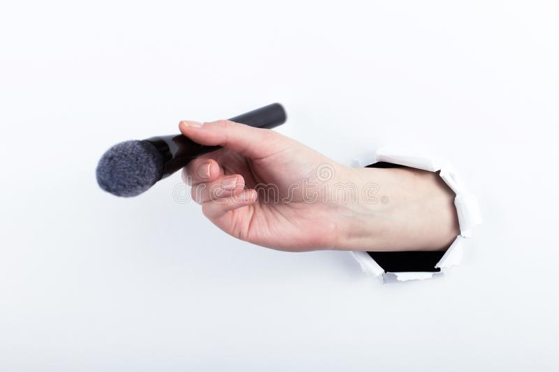 Female hand out of a hole in paper, holding a large powder brush. Isolate on white background royalty free stock photo