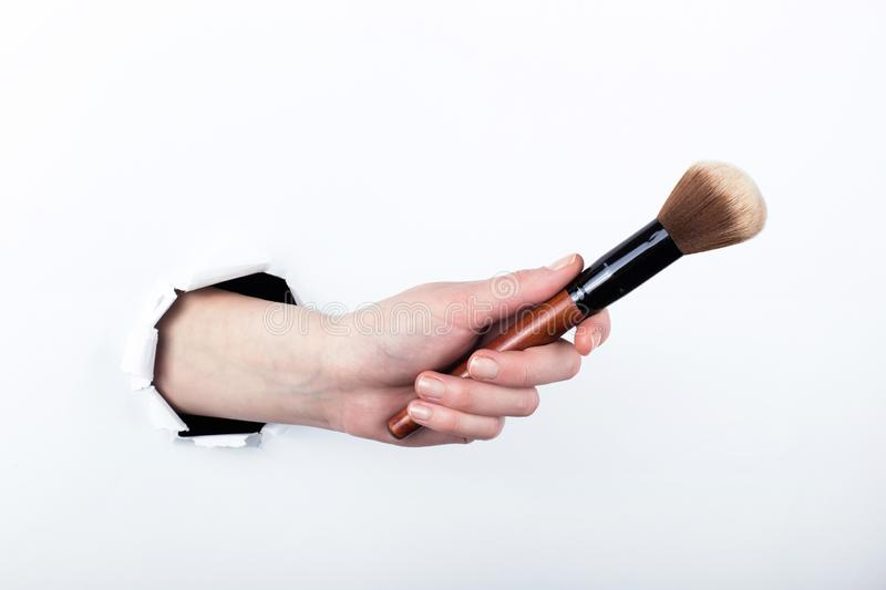 Female hand out of a hole in paper, holding a large powder brush. Isolate on white background stock image