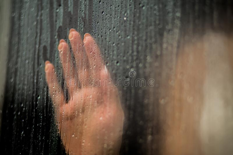 Female hand palm silhouette behind the window with raindrops reaching for the glass. A request for help, depression, stress blurre royalty free stock image