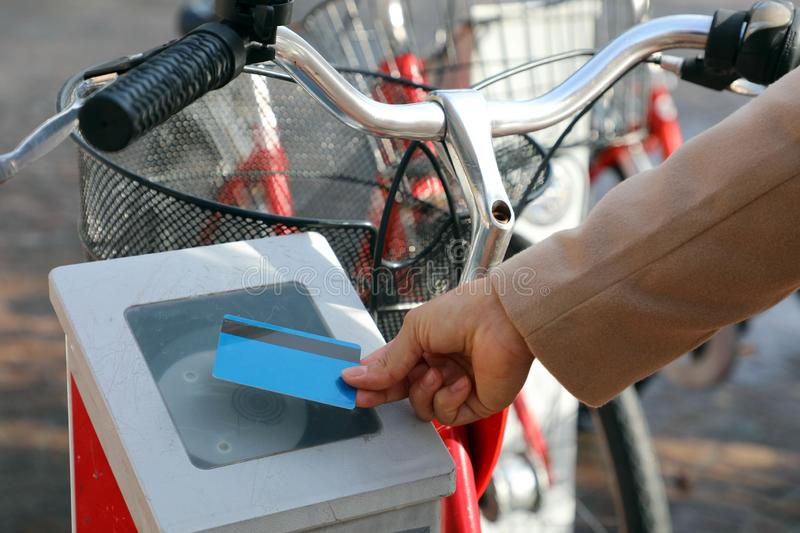 Female hand paying for bike with credit card, using modern contactless system at rental station outdoor.  royalty free stock photos