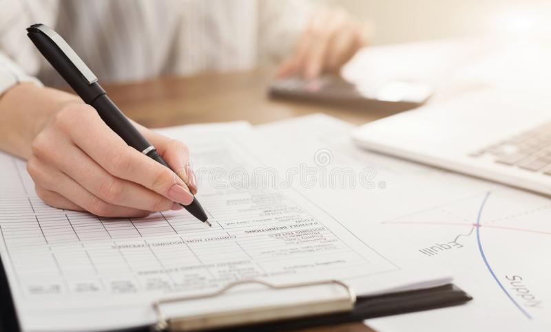 Female hand with pen and business report stock image