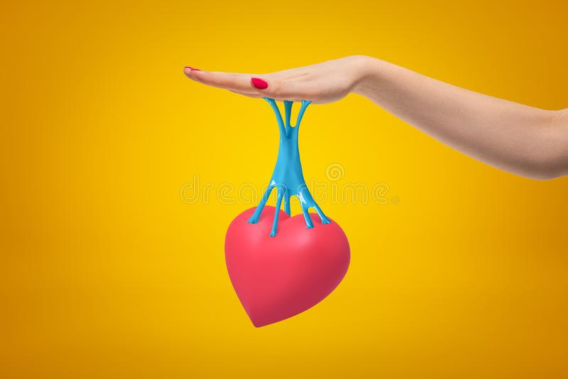 Female hand with pink heart stuck to it with blue sticky slime on yellow background stock photography