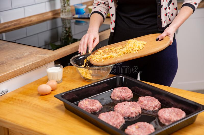 Female hand pouring with grated cheese from cutting board to the plate. Process of cooking the cutlets or meatballs royalty free stock photos